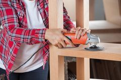 Midsection Of Carpenter Using Sander On Shelf Stock Photo