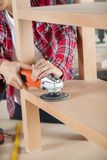 Midsection Of Carpenter Using Sander On Shelf Royalty Free Stock Images