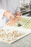 Midsection Of Chef Brushing Ravioli Pasta At Stock Photography