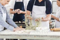 Midsection Of Chefs Preparing Pasta In Kitchen Royalty Free Stock Photo
