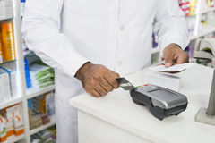 Midsection Of Chemist Holding Receipt While Swiping Credit Card Royalty Free Stock Image