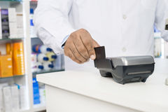 Midsection Of Chemist Swiping Credit Card On Reader. Midsection of male chemist swiping credit card on reader in pharmacy Royalty Free Stock Photos