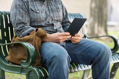 Midsection Of College Student Using Digital Tablet. Midsection of male college student using digital tablet on bench at university campus Stock Photos