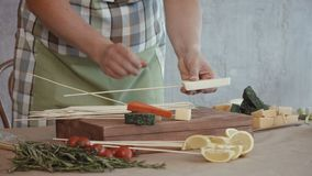 Woman`s hands pinning food ingredients on skrewers. Midsection of cooking woman pinning slices of assorted types of cheese and cherry tomatoes on wooden skewers stock video footage