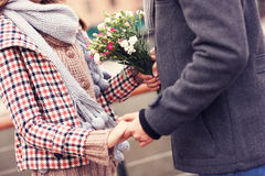 Midsection of a couple holding hands and flowers Royalty Free Stock Image