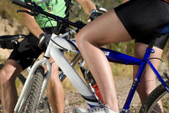 Midsection of couple on mountain bikes stopping for break Stock Photo