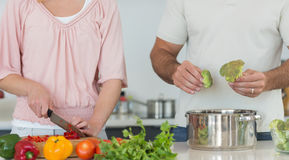 Midsection of couple preparing food together Royalty Free Stock Images