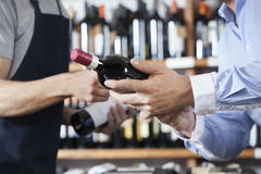 Midsection Of Customer And Salesman With Wine Bottles. Midsection of male customer and salesman with wine bottles in shop royalty free stock photography
