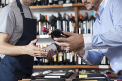 Midsection Of Customer Showing Wine Bottle To Salesman Royalty Free Stock Photo