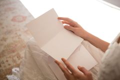 Midsection czyta ślubną kartę panna młoda podczas gdy siedzący w domu obraz stock