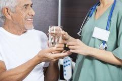 Midsection Daje medycynie I wodzie Starszy pacjent pielęgniarka Zdjęcia Stock