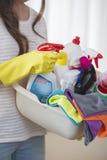 Midsection de la cesta que lleva de la mujer de fuentes de limpieza en casa Fotos de archivo