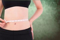 Midsection de la cintura de medición de la mujer contra fondo verde Fotografía de archivo