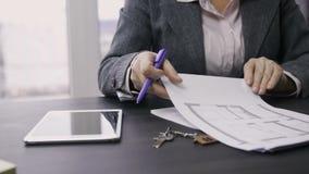 Midsection de la dependienta de sexo femenino que trabaja en la tabla almacen de video