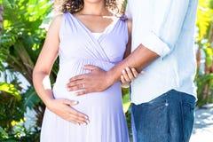 Midsection de la esposa embarazada con el vientre conmovedor del marido Fotografía de archivo libre de regalías