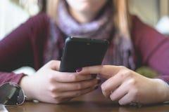 Midsection de la muchacha que comprueba el smartphone fotografía de archivo