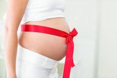 Midsection de la mujer con la cinta roja en el abdomen Fotografía de archivo