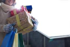 Midsection de la mujer con los regalos apilados y la ventana que hace una pausa de las compras durante invierno Imagen de archivo libre de regalías