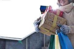 Midsection de la mujer con los regalos apilados y la ventana que hace una pausa de las compras durante invierno Foto de archivo libre de regalías