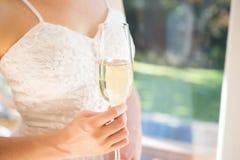Midsection de la novia que sostiene el champán mientras que hace una pausa la ventana Foto de archivo libre de regalías