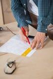 Midsection de la tabla de Drawing Blueprint At del carpintero imagenes de archivo