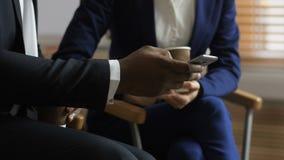 Midsection de los colegas diversos que miran el tel?fono almacen de metraje de vídeo
