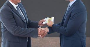 Midsection de los hombres de negocios que sostienen el dinero que representa concepto de la corrupción imagen de archivo
