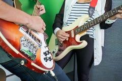 Midsection de los miembros de la banda que tocan las guitarras fotos de archivo