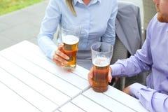 Midsection de los pares del negocio que celebran los vidrios de cerveza en el restaurante al aire libre Imagen de archivo libre de regalías