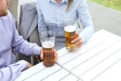 Midsection de los pares del negocio que celebran los vidrios de cerveza en el restaurante al aire libre Fotografía de archivo