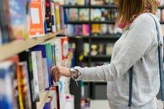 Midsection de una muchacha que escoge los libros en la biblioteca imagen de archivo libre de regalías