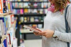 Midsection de una muchacha que escoge los libros en la biblioteca foto de archivo libre de regalías