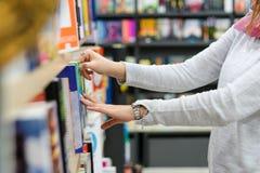 Midsection de una muchacha que escoge los libros en la biblioteca fotografía de archivo