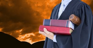 Midsection dei libri e del martelletto della tenuta dell'avvocato contro il cielo drammatico Immagine Stock