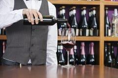 Midsection del barista Pouring Red Wine in vetro Fotografia Stock