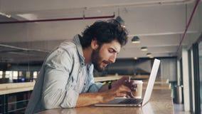 Midsection del blogger que usa el ordenador portátil en la tabla almacen de video