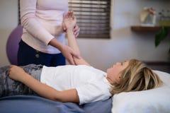 Midsection del brazo de examen del terapeuta de sexo femenino con el muchacho que miente en cama fotografía de archivo libre de regalías