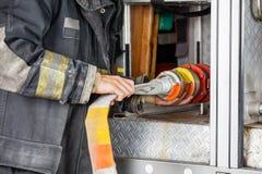 Midsection del camion di Adjusting Hose In del pompiere immagine stock libera da diritti