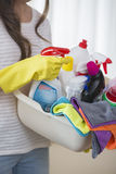 Midsection del canestro di trasporto della donna dei rifornimenti di pulizia a casa Fotografie Stock
