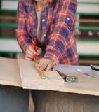 Midsection del carpintero Measuring Wood foto de archivo libre de regalías