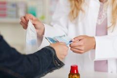 Midsection del cliente de Receiving Money From del farmacéutico para el médico Imagen de archivo libre de regalías