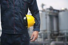 Midsection del giovane operaio che tiene un elmetto protettivo giallo all'aperto con la fabbrica nei precedenti immagine stock libera da diritti