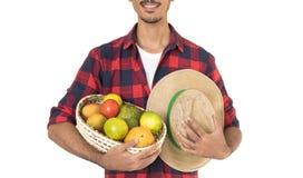 Midsection del granjero que sostiene una cesta de frutas Imagen de archivo