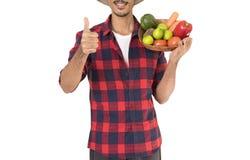 Midsection del granjero que sostiene una cesta de verduras Imagen de archivo libre de regalías