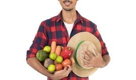 Midsection del granjero que sostiene una cesta de verduras Fotos de archivo