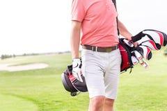 Midsection del hombre con el bolso de club de golf que se coloca en el curso imagen de archivo libre de regalías