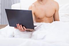 Midsection del hombre descamisado que sostiene el ordenador portátil en cama Imagen de archivo