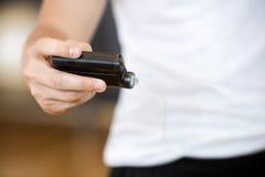 Midsection del hombre que sostiene el monitor de la glucosa en gimnasio foto de archivo libre de regalías