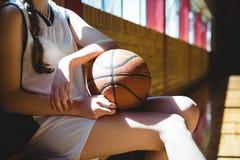 Midsection del jugador de básquet de sexo femenino que se sienta por la pared Imagen de archivo