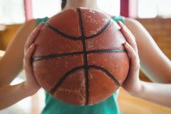 Midsection del jugador de básquet de sexo femenino que sostiene la bola Imagen de archivo